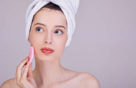 Gorgeous girl with make up and shoulders posing on gray background with cleaning sponge, skin care concept, beauty photo. Caring and youthful skin. Body care. Spa care.