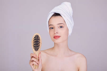 A young girl in a white towel on her head, after a shower, holds a wooden comb in her hands and looks into the frame. Beauty and care concept. Photo on a light background.