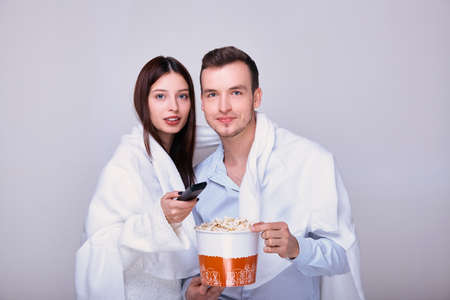 Laughing couple, man and woman watching tv, comedy show or movie and eating popcorn snack, family, man and woman enjoying free time, weekend together.