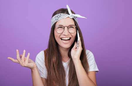 A young girl with dark hair and green eyes in a white T-shirt with round glasses, in a vest and a bandage on her head speaks on the phone and laughs. Expression. Young student. Photo on background.