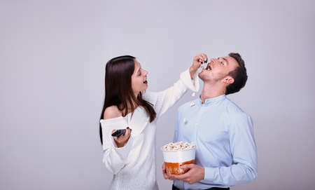Beautiful young couple in love while watching movie at the home theater frolic. The girl holds the remote control from the TV and spills popcorn into the guy's mouth, and guy holds a basket of popcorn