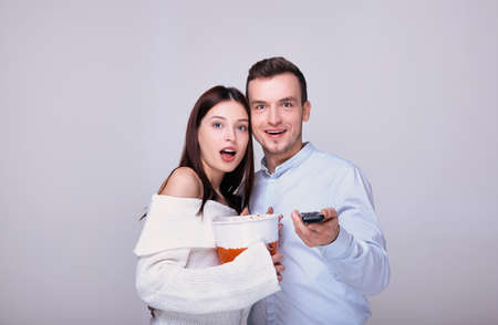 A young girl in a white sweater opened her mouth in surprise, holds a bucket of popcorn in her hands and snuggles up to a cheerful guy in a blue shirt who is holding a TV remote control.