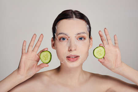 Close up gentle sophisticated calm girl in a moisturizing mask with a fresh cucumber on the face in the background serious with open eyes, hands holds a cucumbers in both hands near her face.