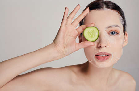 Close up, girl in a moisturizing mask with a fresh cucumber on the face in the background serious with open eye and right hand holds a cucumber near face