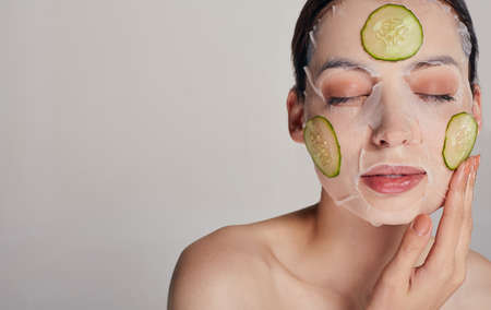 Close up gentle sophisticated calm girl in a moisturizing mask with a fresh cucumber on the face in the background serious with closed eyes, one hand near her face touching cucumber.