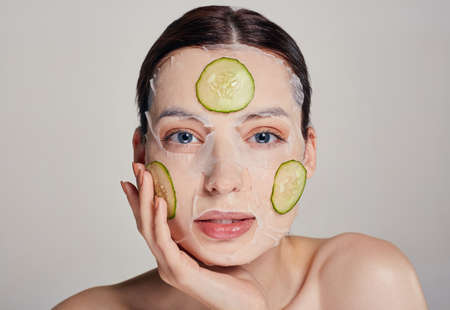 Close up gentle sophisticated serious calm beauty girl in a moisturizing mask with a fresh cucumber on the face in the background, hand near her face looking straight