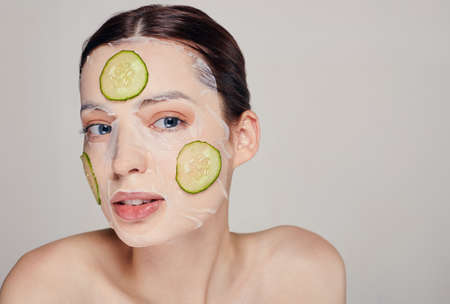 Wellness. Close up gentle sophisticated mysterious girl in a moisturizing mask with a fresh cucumber on the face in the background looking away.