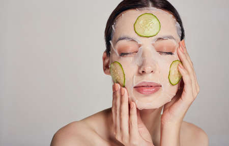 Close up. Gentle sophisticated calm girl in a moisturizing mask with a fresh cucumber on the face in the background serious with closed eyes and hands near her face