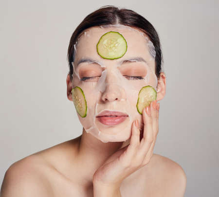 Close up gentle sophisticated girl in a moisturizing mask with a fresh cucumber on the face in the background serious calm beauty with closed eyes, left hand near her face Stock Photo