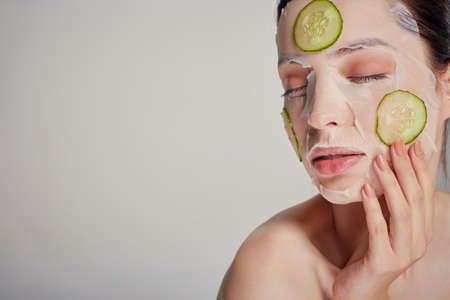 Close up gentle sophisticated girl in a moisturizing mask with a fresh cucumber on the face in the background serious with closed eyes, hand near her face