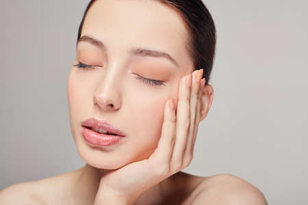 An elegant sophisticated beautiful girl with full lips, brown hair and clean delicate skin on the gray background. Lady put her head on her hand. Close eyes. Spa, face skin care. Wellness. Reklamní fotografie