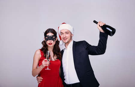 Beautiful loving couple wearing evening outfit. Happy young couple in love celebrate the New Year and drink shampassnoe. Laughing couple on a white background at the New Year's party.