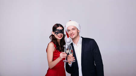 A lady in a red dress with red lips in a black lace mask and a guy in a Santa hat drink champagne on a white background and celebrate the New Year. Fashionable couple celebrate Christmas together.