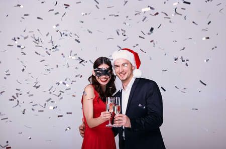 Party for two. Young couple bonding and dancing while standing against white background with confetti. Young beauty in a red dress and a carnival mask drinks champagne with a guy in a Santa hat. Stock Photo
