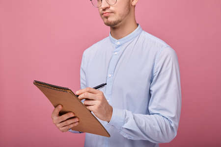 A young student in a pale blue shirt with glasses with a brown flipchart in one hand and a black ballpoint pen in the other. He writes, studies, thinks, a student writing. Close up, copy space.