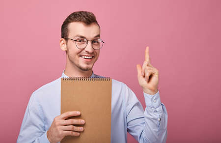 Focus on finger. A young student in a gently blue shirt with glasses holds, in his hand a brown loose-leaf notebook and hi looks into frame happy, on a pink background. Finger up, bottom. Greate idea.