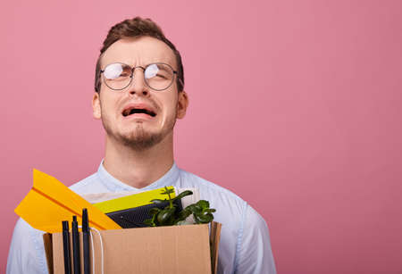 A young pretty guy in a sky blue shirt and computer glasses stands on a pink background with a cardboard box with pens, plant and different things in his hands. Dismissal. Fired. Man is disappointed.