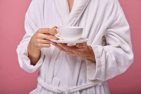Un sleepy young man in a sleeping mask on his head in a white coat with a with a cup of coffee in his hand. Awakening, morning mail. Pink background.