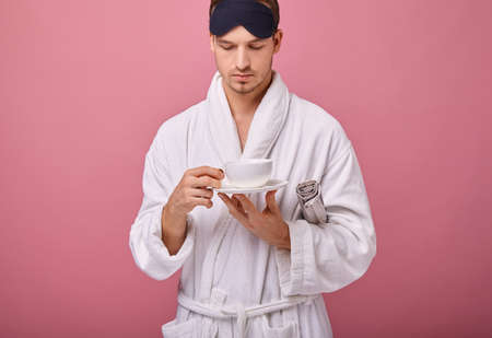 Woken up man in a sleeping mask on his head in a white coat with a tied belt with a newspaper under his arm, with a cup of coffee in hands. Awakening, morning mail. Copy space.