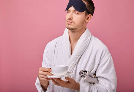 Sleepy man in a sleeping mask on head in a white coat with a newspaper under his arm, smiling at the camera with a cup of coffee in hands. Awakening, morning mail. Copy space. Looking sideway calm.