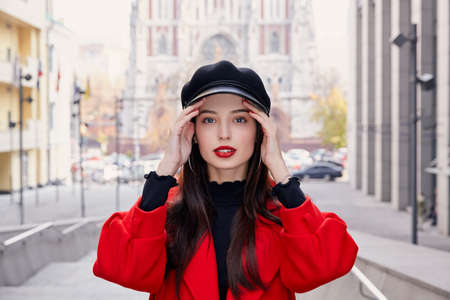 Stunning charming unsurpassed girl with bright red lips and brown hair in a cool red coat in a black cap looks directly into the frame and holds both hands near the temples. City traffic in background
