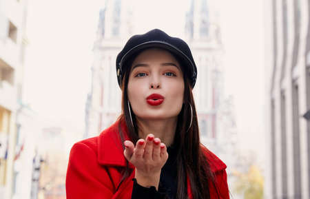 A stunning charming unsurpassed girl with bright red lips and brown hair in a cool red coat and a funny cap sends you an air kiss. In the background a city and buildings. Copy space