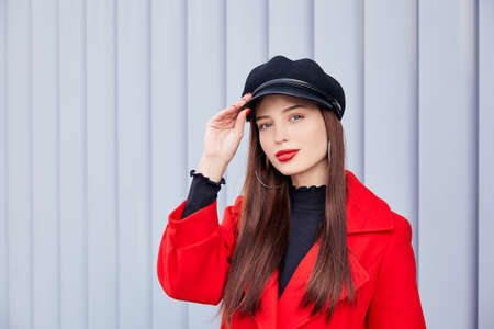 Ravishing lady stands on a striped gray background. Admirable entrancing girl with big earrings rings on the ears, in red autumn coat and black golf holds her black kepi by hand and looks at frame.