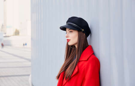 Ravishing lady stands on a striped gray background. Sweetly pretty entrancing girl in kepi, in red autumn coat and black golf thoughtfully looks forward from herself.