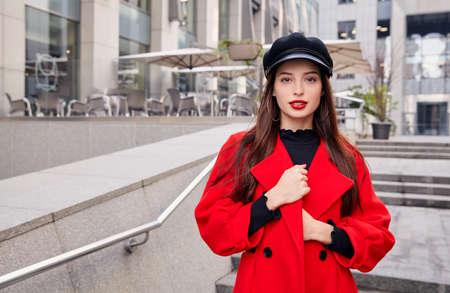 Lovely charming ravishing calm girl in black kepi, red autumn coat and black golf in earrings rings holds her overcoat by hands near building in cloudy weather at town.