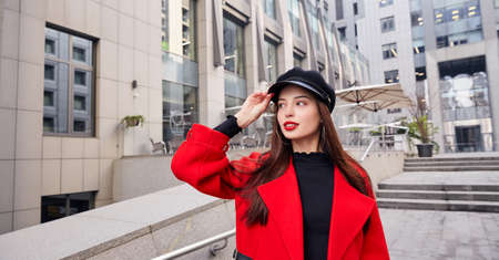 Admirable ravishing dreamy girl in earrings rings, in red autumn coat and black golf holds her black kepi by hand and looks at side. Lady stands near building on the steps.