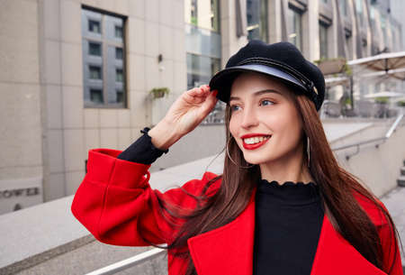 Ravishing luscious delightsome girl in red overcoat and black sweater holds her kepi by hand, looks into the distance and smiles. Woman stands on the steps.