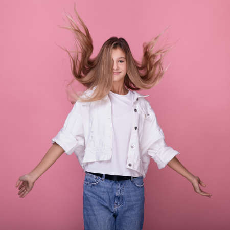 Cheerful teenager girl with flying hair smiling and posing on a pink background. A young lady in a white denim jacket and blue jeans looks at the camera and smiles.