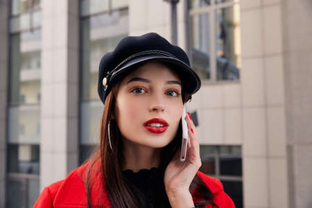 Cryptic charming calm lady with full red lips in kepi talks on white cellphone and looks straight at frame enigmatically. Woman dressed at black sweater and bright red coat.