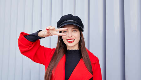 Likable beauty lady holds a peace sign near her eye and smiling. A girl stands on a striped gray background in a red autumn coat and a black kepi on her head. Copy space.