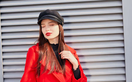 Engaging pleasing lady enjoys the last autumn sunshine with closed eyes against a gray striped background. Pretty beauty in a catchy red coat and black cap with a visor on her head.