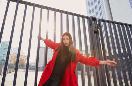 Alluring engaging girl hung on the gate, holding on to the bars with one hand, and the other hand turned away. Lovely endearing lady with a playful mood in warm red coat and black golf with look