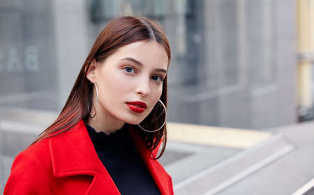 Charming stunning mysterious charming girl with brown hair and blue eyes in black golf and a red autumn coat looks sexy and tender in the frame. Cloudy weather, city backgroung, gray building.