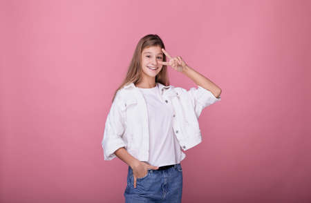 A girl with long blonde hair in fashionable clothes is smiling and posing on the background. Teenager shows a peace sign. The blonde in a white jacket smiles on a pink background. Stock Photo