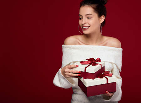 Joyful woman holding a lot of boxes with gifts on a red background. A sweet, in a good mood white girl with dark hair holds gifts and smiles with a wide snow-white smile.