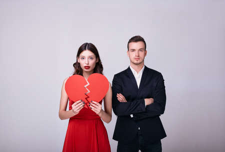 Beautiful young woman in a red dress holds a broken heart from red paper in her hands. Next to the girl is a young man in a dark suit, arms crossed, looking straight. Broken love. Copy space. Stock Photo