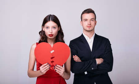 Elegant luxurious pair of young lovers in evening dresses pose with a broken red heart on a white background. The concept of Valentine's Day, broken love, is no longer together. Standard-Bild