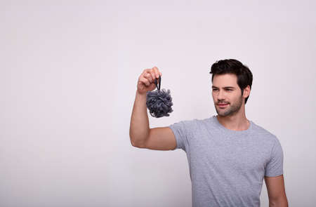 A handsome gallant young man with brown hair and dark eyes holds in his right hand a gray washcloth for a shower and looks at it. The concept of men's hygiene, male beauty. Copy space.