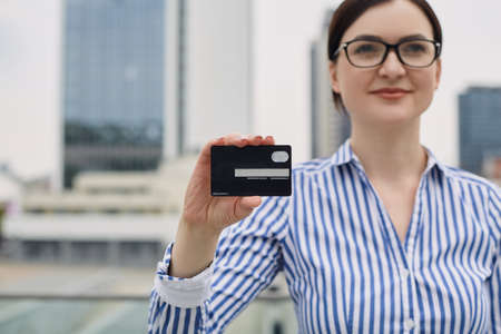 Smiling pretty business lady in a striped shirt and glasses standing with a credit card in her right hand against the background of the city. Payment, installment, purchase every day Stock Photo