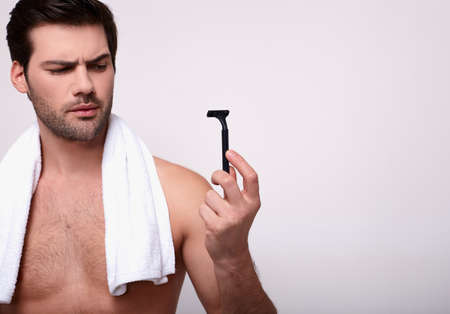 Macho guy with a white towel thrown over his neck and black razor in his hand. Cool man looks at a razor with one eyebrow raised. Hygiene, morning routines. Copy space.