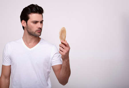 A young attractive martyr with dark thick hair and a beard, in a white T-shirt, holding a wooden comb in his hand and looking at it. The concept of healthy hair and fallout hair. Copy space.