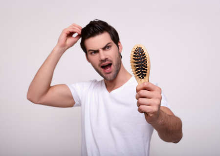 Close-up of a wooden comb, and in the background a young guy with dark eyes holds on to his head and screams. A man with a hair loss problem. Medical and shampoo product concept. 写真素材