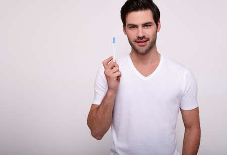 A handsome young man in a white T-shirt is going to brush his teeth, engaged in morning routine, oral hygiene. The concept of health, healthy teeth, dentistry, bleeding gums. Copy space.
