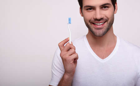 Man with a toothbrush. Cropped image of a young white man in a white T-shirt holding a toothbrush and smiling while standing against a gray background. A man does oral hygiene. Copy space.