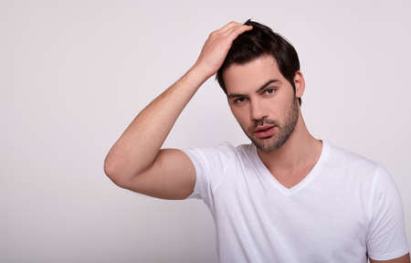 A chic impressive man, a fashion model, with a stylish hairstyle, in a white T-shirt looks into the camera and touches his hair. A young white guy sexually poses on a white background.