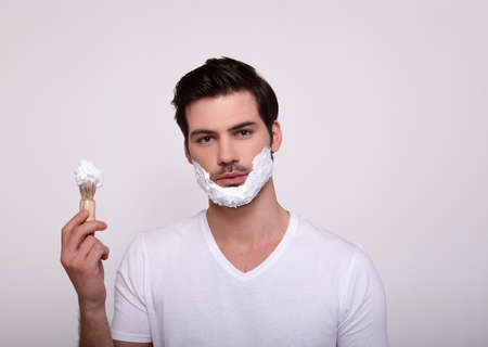 A serious young man with a beard and dark hair, with shaving foam on his face, in a white T-shirt, holding a shaving anoint in his left hand. A man does a morning routine.